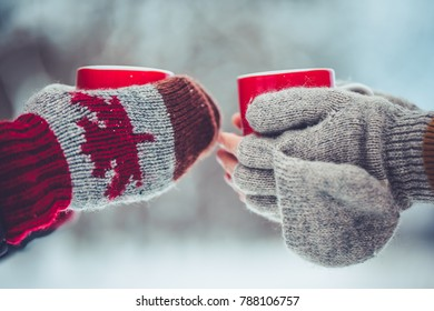 Cropped image of dad and daughter are holding cups and drinking tea outdoor in winter. Enjoying spending time together. Family concept.