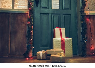 Cropped image of decorated house facade with presents from Santa Claus before Christmas. Gift boxes are lying on the porch in New Year Eve.