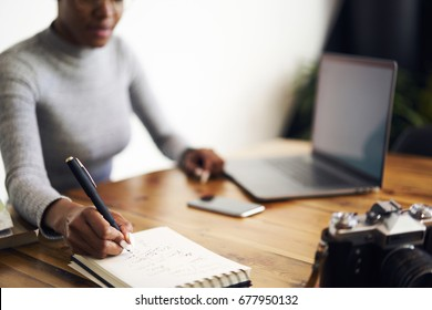 Cropped image of defocused afro american web designer doing remote job in office using modern laptop computer drawing sketch and blueprints, selective focus on handwriting with pen in notepad