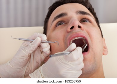 Cropped image of dentist examining male patient's mouth in clinic