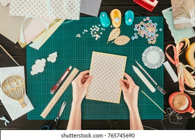 cropped image of designer holding template for scrapbooking postcard
