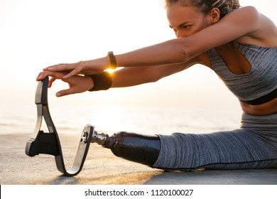 Cropped image of disabled athlete woman with prosthetic leg doing stretching exercises while sitting at the beach