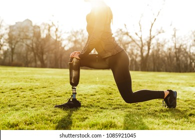 Cropped image of disabled athletic girl in black sportswear doing lunges and stretching prosthetic leg on grass