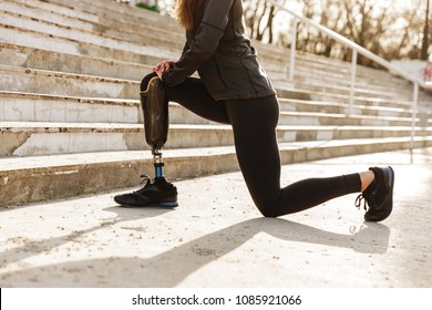 Cropped image of disabled sporty woman in tracksuit doing sports and sit ups with bionic leg in stadium outside