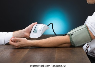 Cropped image of doctor checking blood pressure of businessman at table