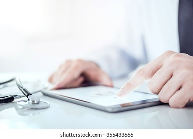 Cropped image of a doctor working on his digital tablet.He is showing digital tablet with blank screen