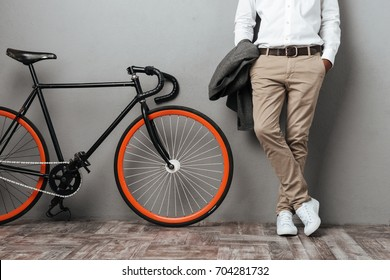 Cropped image of dressed half mens body standing near a bicycle isolated over gray background