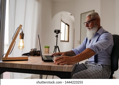 Cropped image of a elderly man working on his laptop in a studio, rear view of business man hands busy using laptop at office desk, male  typing on computer and drinking good express coffee. Image