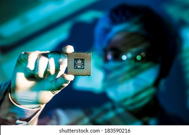 Cropped image of an engineer holding computer microchip on the foreground