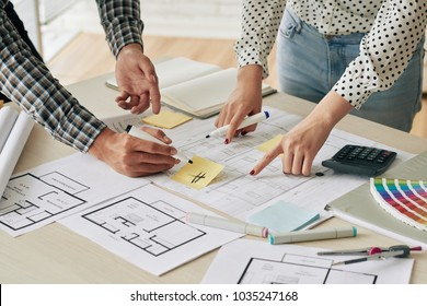 Cropped image of engineers discussing blueprint of new building