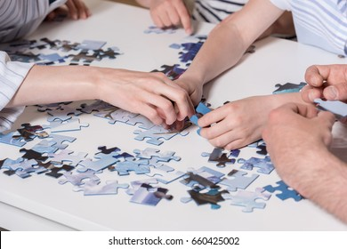 Cropped image family playing with puzzle on table at home together
