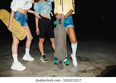 Cropped image of fashion multiethnic girls in streetwear riding skateboards at night outdoors