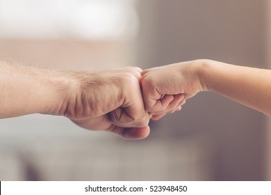 Cropped image of father and son touching fists