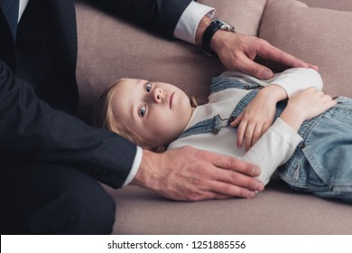 cropped image of father in suit taking care of sick daughter on sofa in living room
