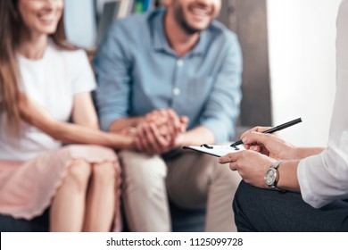 cropped image of female counselor writing in clipboard while couple sitting on sofa and holding hands of each other in office