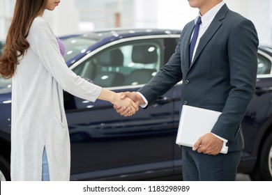 Cropped image of female customer shaking hand of salesman after buying new car