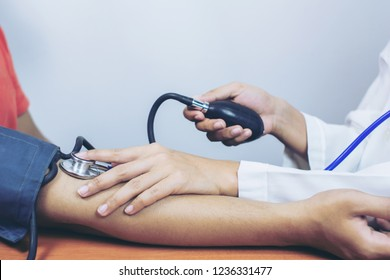 Cropped image of female Doctor checking old man patient arterial blood pressure.Selective focus .Health and Medical concept