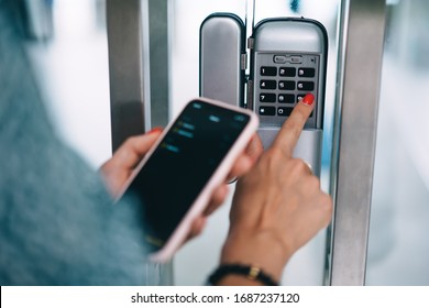 Cropped image of female entering secret key code for getting access and passing building using application on mobile phone, woman pressing buttons on control panel for disarming smart home system