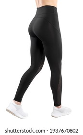 Cropped image of a female figure in tight black leggings take a side step, over white background. Vertical view.