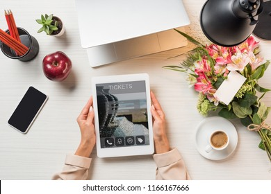 cropped image of female freelancer holding digital tablet with tickets on screen at table with coffee cup, gadgets and flowers with greeting card