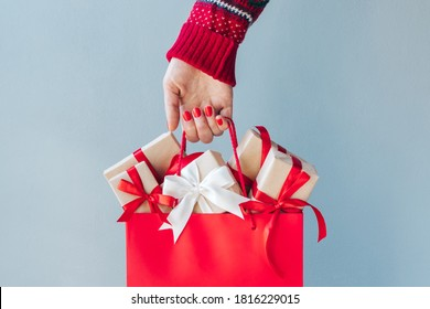 Cropped image of female hand with red polished nails holding shopping bag full of christmas gift boxes. Holiday sale concept.