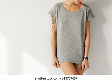 Cropped image of female hipster with perfect body wearing grey oversize T-shirt, posing as model for fashion collection with copy space for your text or advertising information. People and style