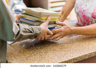 Cropped image of female librarian taking books from boy at checkout counter in library
