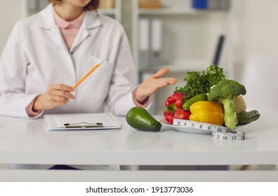 Cropped image female nutritionist points to a plate of fresh vegetables and a tape measure on her desk. Concept of a healthy lifestyle, body care and weight loss. Selective focus. Blurred background.