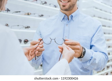 cropped image of female oculist giving eyeglasses to young man in ophthalmic shop