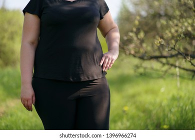 Cropped image of female overweight obese body. Fat woman in sportswear standing outdoors. Weight loss concept