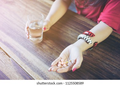 Cropped image of female patient taking medicine for illness. capsule and glass of water on wood table at home. Health care and medical treatment concept.