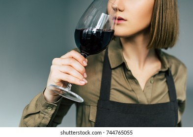 Cropped image of Female sommelier examining red wine