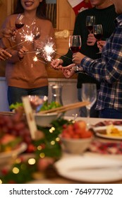 Cropped image of firends with sparklers and wine glasses at New Year party