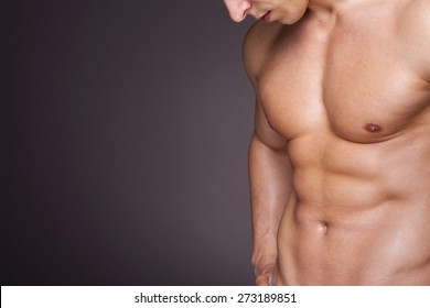 Cropped image of fit man showing six pack abs