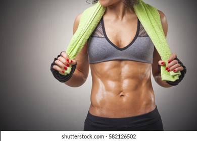 Cropped image of a fit woman posing with a green towel on grey background