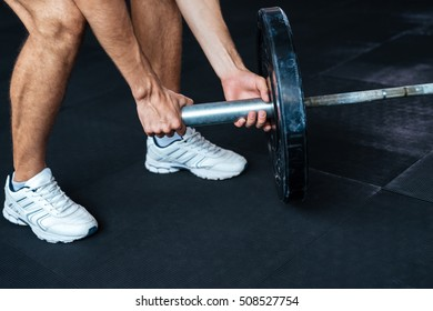 Cropped image of fitness man with barbell. preparing to raise