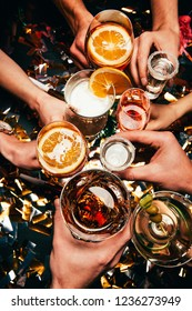 cropped image of friends clinking by glasses with various alcoholic cocktails at table covered by golden confetti