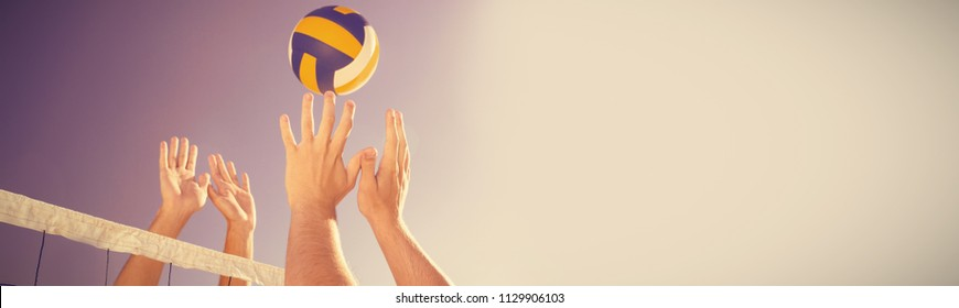 Cropped image of friends playing volleyball at beach