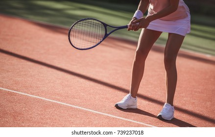 Cropped image of girl holding tennis racket while playing tennis on court outdoors