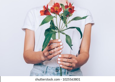 Cropped image of a girl in jeans and a T-shirt holding a red flower in her hands with a manicure on a white background