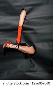 cropped image of girl in orange glove holding polka dot sock through holes in black paper