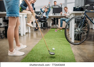 cropped image of girl playing in mini golf with colleagues at modern office