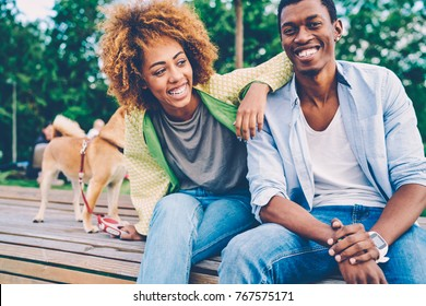Cropped image of good looking afro american couple dressed in stylish clothes fooling around during summer walk at street.Positive man and woman friends laughing and joking during sitting on bench