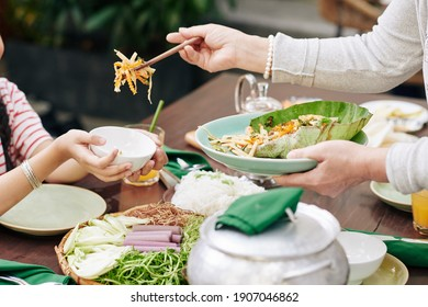 Cropped image of grandmother putting salad in plate of granddaughter at family dinner