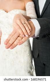 Cropped image of groom displaying their wedding rings