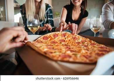 Cropped image of a group of friends eating big pizza and drinking white vine while having a home party