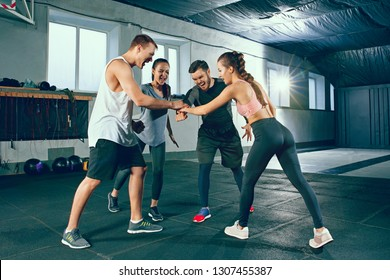 Cropped image of group of sporty muscular people are having rest after or before working out in gym. Healthy lifestyle and friendship concept