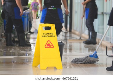 Cropped image of group of woman in protective gloves using a flat wet-mop and machine while cleaning floor