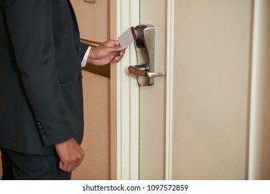 Cropped image of guest opening door of hotel room with electronic key
