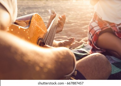 Cropped image of a guy playing guitar for his friends at the beach